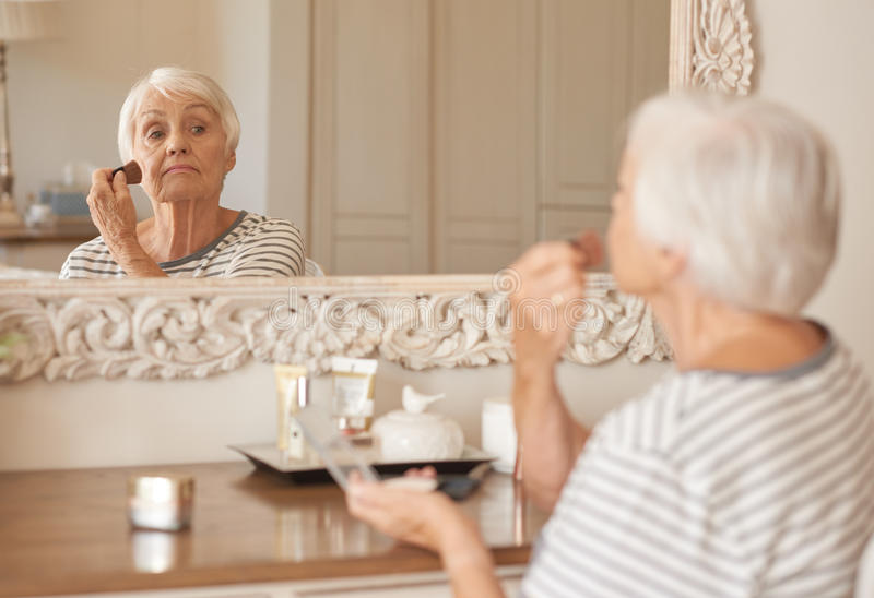 Donna senior che applica trucco alla sua guancia in uno specchio immagini stock