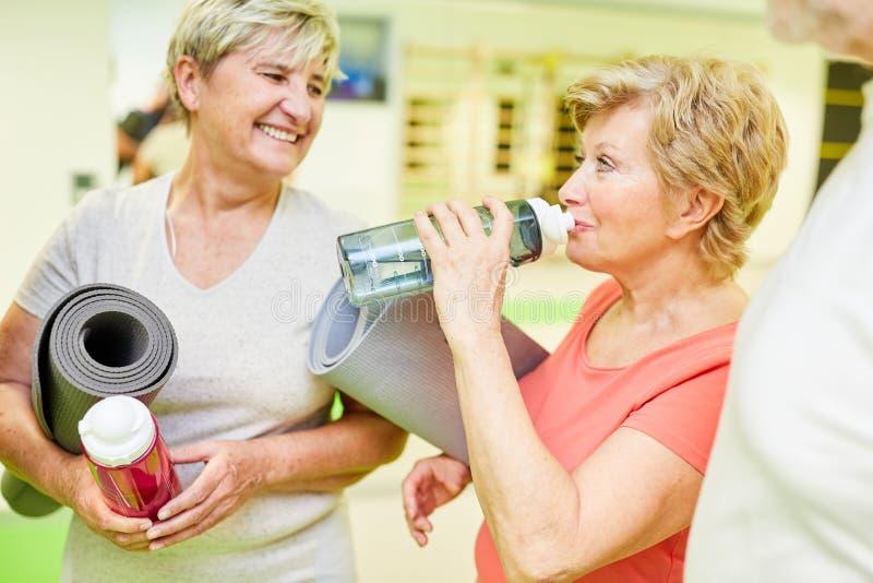 Donna senior che beve da una bottiglia di acqua durante una pausa fotografia stock
