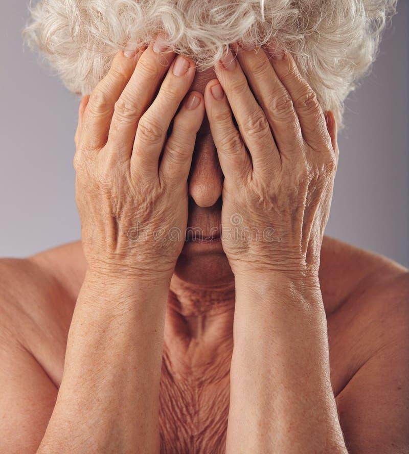 Donna senior che copre il suo fronte di mani fotografia stock libera da diritti