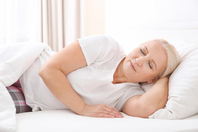 Donna senior che dorme sul cuscino bianco fotografia stock libera da diritti
