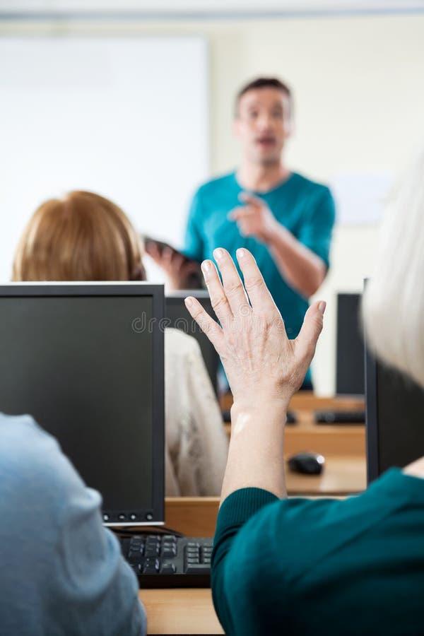 Donna senior che fa domanda nella classe del computer fotografia stock