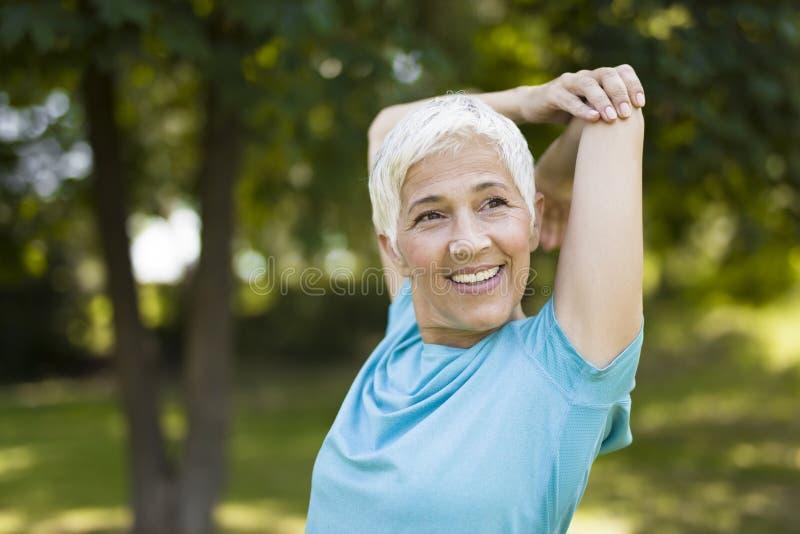Donna senior che fa esercizio per l'allungamento della mano nel parco fotografie stock libere da diritti