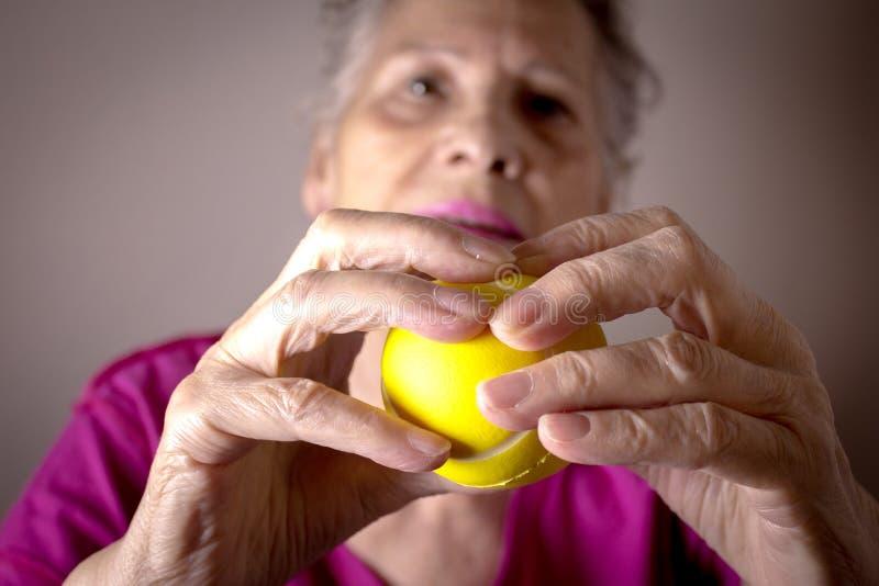Donna senior che fa gli esercizi con una palla in sue mani immagini stock
