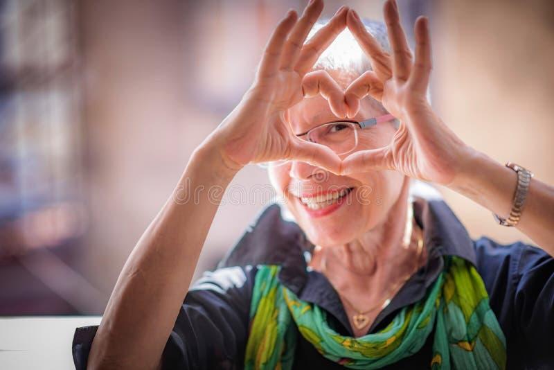 Donna senior che fa una forma del cuore, sveglio ed adorabile fotografia stock libera da diritti