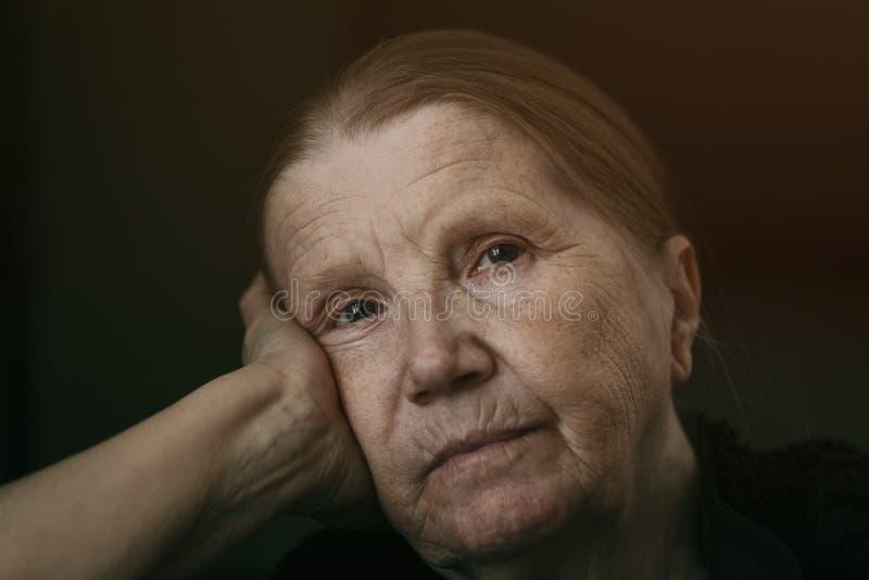 Donna senior che guarda alla macchina fotografica con lo sguardo triste immagine stock