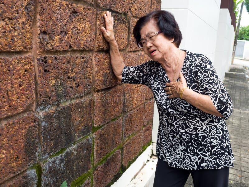 Donna senior che ha dolore toracico e suo seno della tenuta a causa di infarto del cuore Concetto di attacco di cuore immagine stock