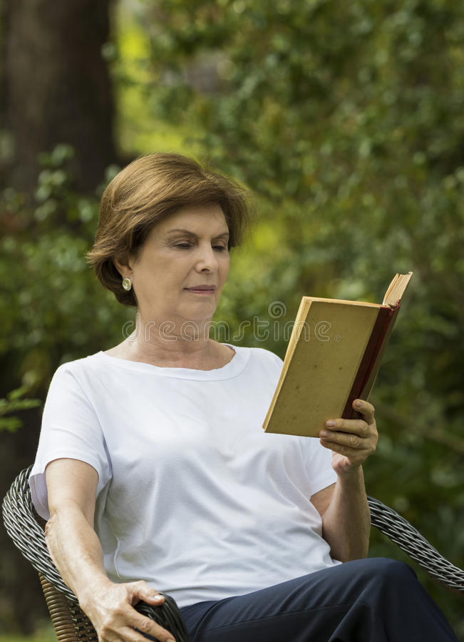 Donna senior che legge un libro in un giardino immagine stock libera da diritti