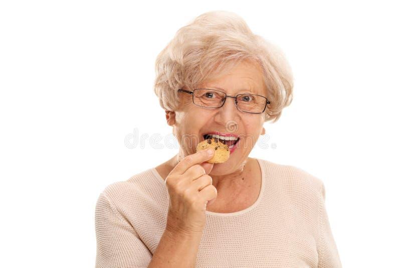 Donna senior che mangia un biscotto fotografie stock libere da diritti