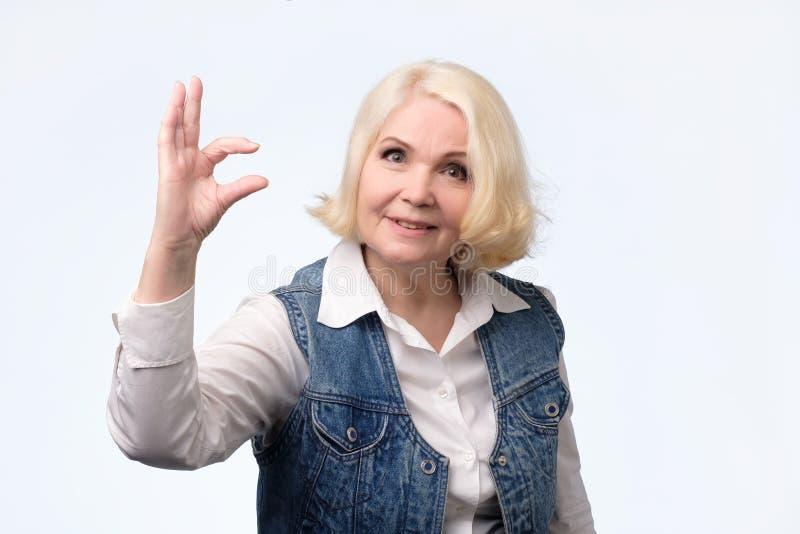 Donna senior che mostra segno di piccola dimensione con le dita fotografia stock libera da diritti