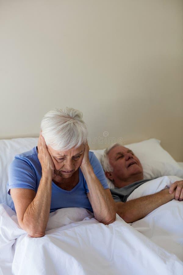 Donna senior che ottiene di disturbo con l'uomo che russa sul letto fotografia stock