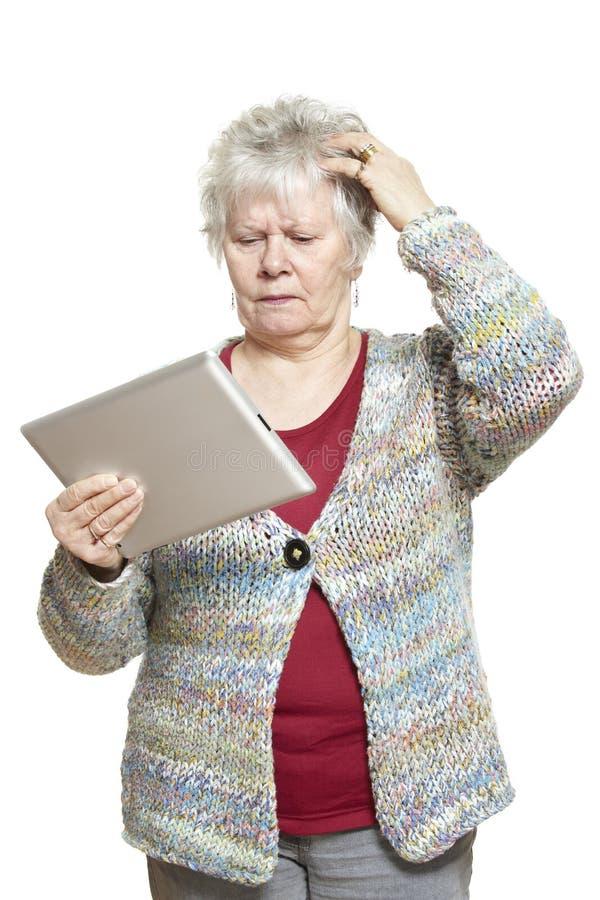 Donna senior che per mezzo del computer della compressa che sembra sconcertante immagine stock libera da diritti
