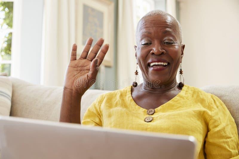 Donna senior che per mezzo del computer portatile per collegarsi con la famiglia per la video chiamata fotografia stock libera da diritti
