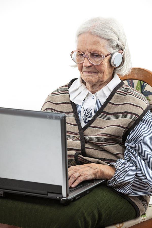 Donna senior che per mezzo del computer portatile sopra bianco fotografie stock