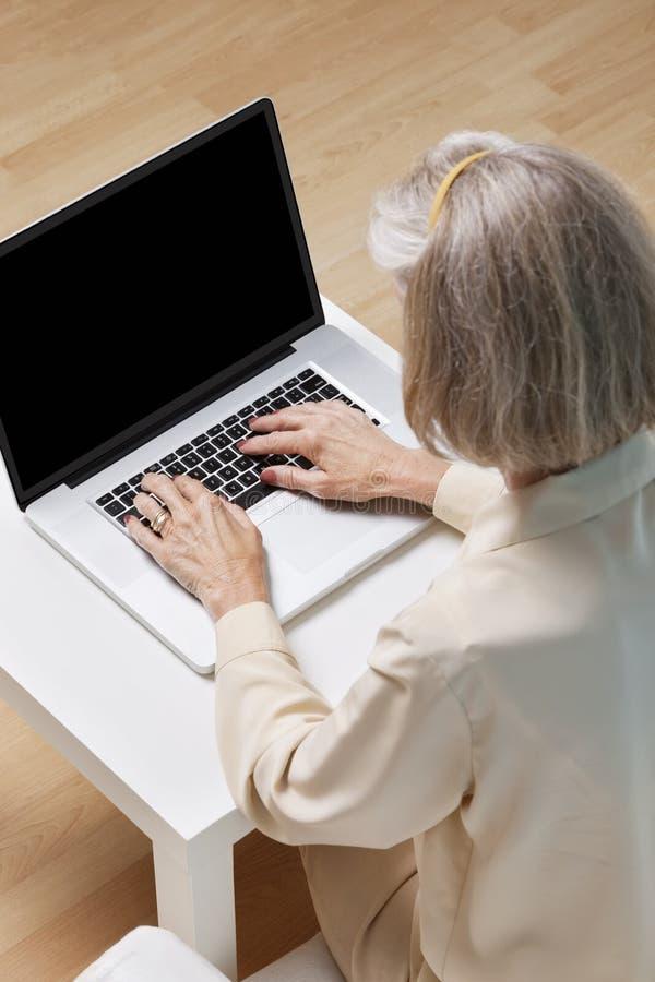 Donna senior che pratica il surfing la rete sul computer portatile a casa fotografia stock
