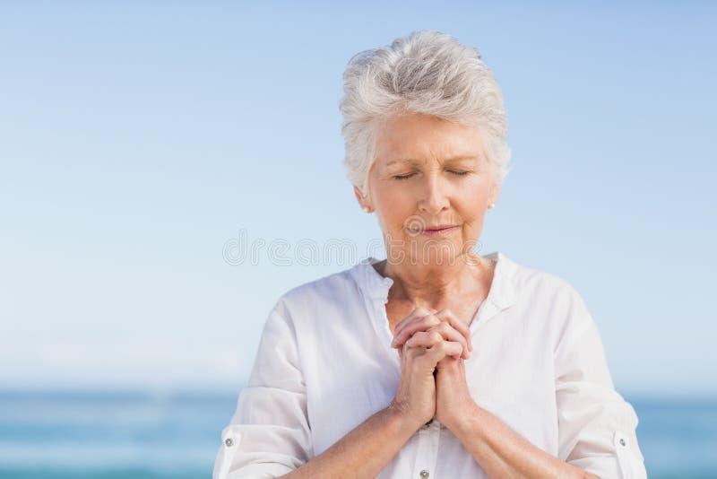 Donna senior che prega sulla spiaggia fotografia stock libera da diritti