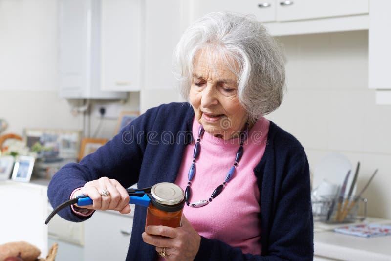Donna senior che prende coperchio fuori dal barattolo con l'aiuto della cucina fotografie stock
