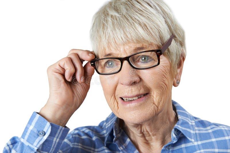 Donna senior che prova sui nuovi vetri fotografie stock libere da diritti