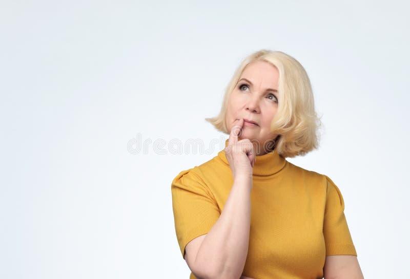 Donna senior che sembra sicura su con il sorriso con la mano sollevata sul mento fotografie stock libere da diritti
