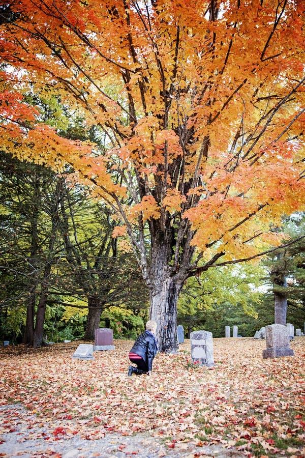 Donna senior che si addolora nel cimitero fotografia stock