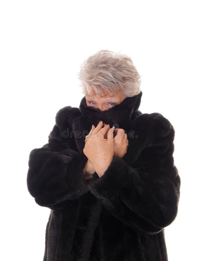 Donna senior che si nasconde in sua pelliccia fotografia stock libera da diritti