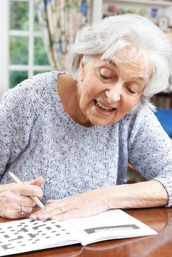 Donna senior che si rilassa con il cruciverba a casa fotografie stock libere da diritti