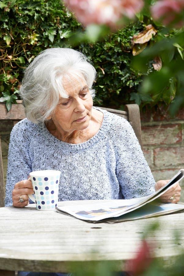 Donna senior che si rilassa in giornale della lettura del giardino immagini stock