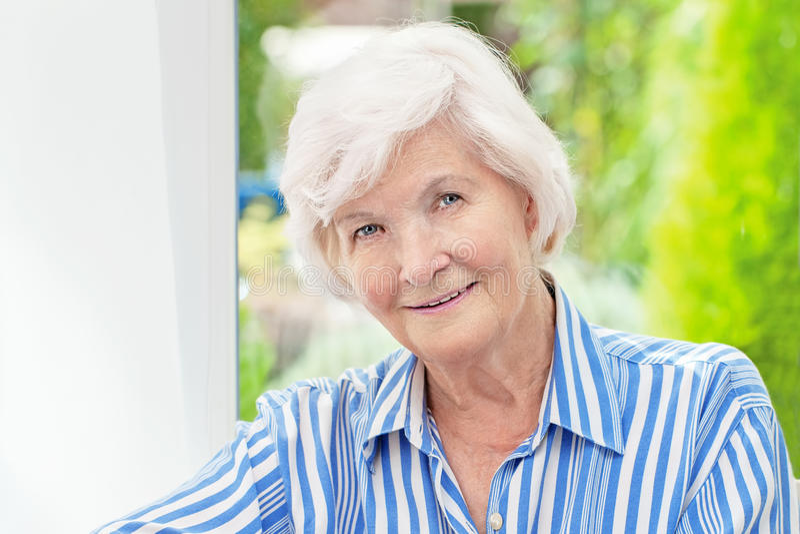 Donna senior che si siede a casa fotografia stock