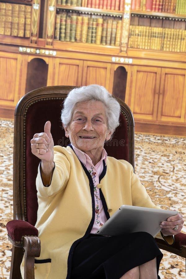 Donna senior che si siede nella sua lettura del salone su una compressa immagine stock libera da diritti