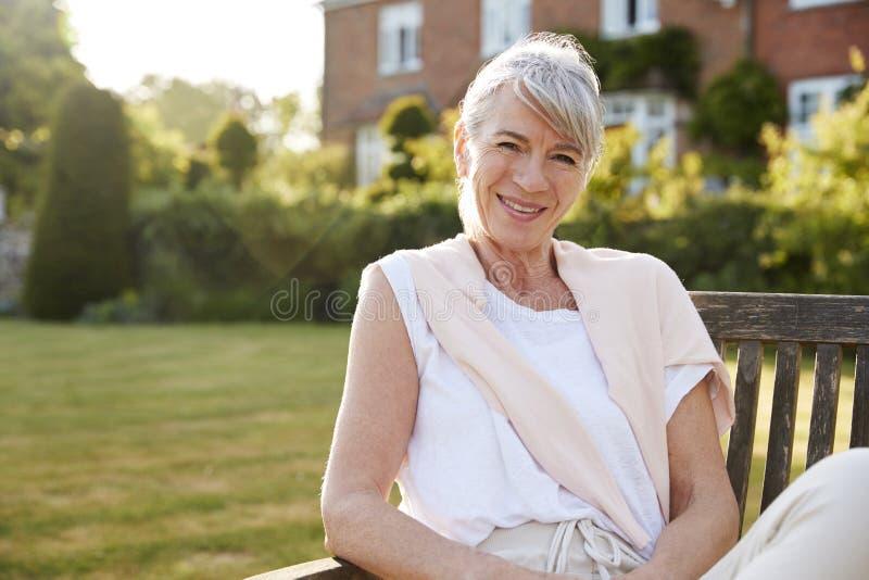 Donna senior che si siede sul banco del giardino alla luce solare di sera fotografia stock libera da diritti