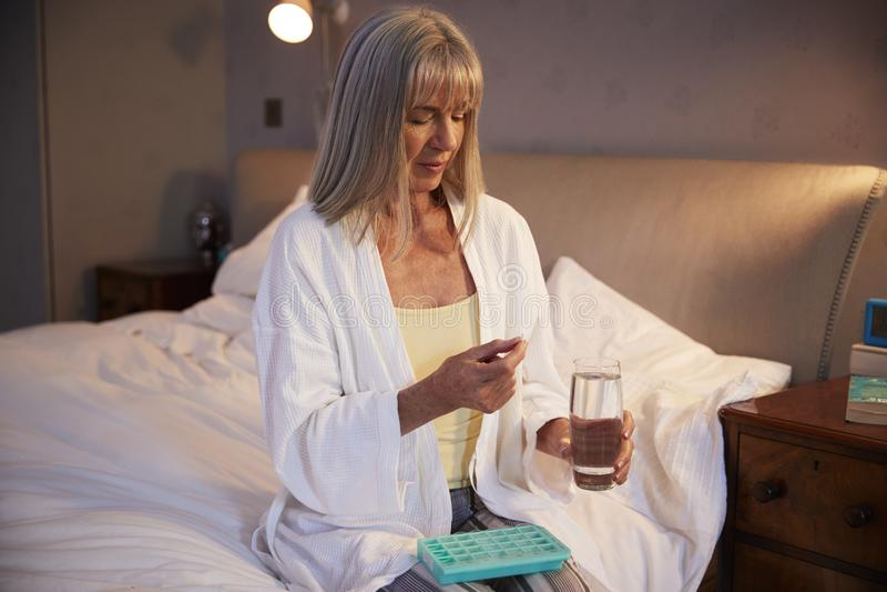 Donna senior che si siede sul letto a casa che prende farmaco immagine stock libera da diritti