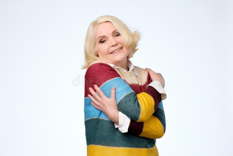 Donna senior che soddisfa espressione facciale felice, abbracciantesi fotografia stock