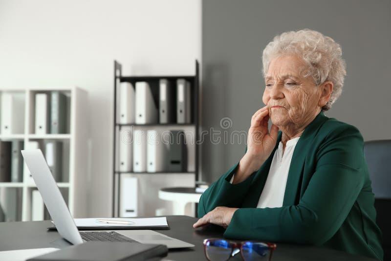 Donna senior che soffre dal mal di denti mentre sedendosi alla tavola con il computer portatile fotografia stock