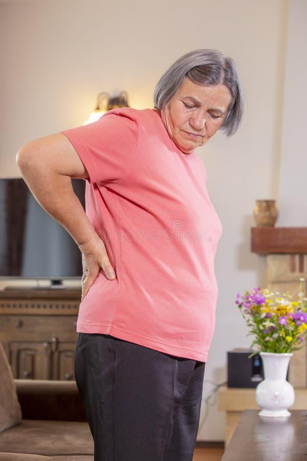 Donna senior che soffre dal mal di schiena a casa fotografia stock libera da diritti