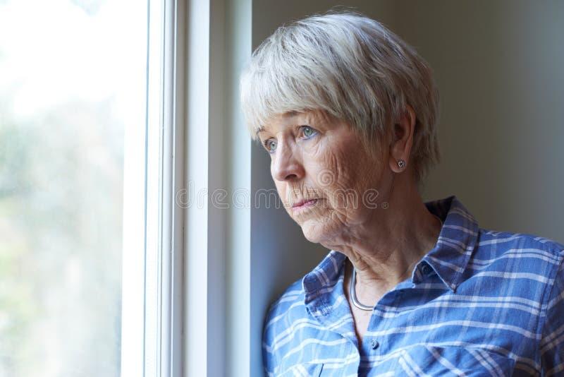 Donna senior che soffre dalla depressione che guarda dalla finestra immagini stock libere da diritti