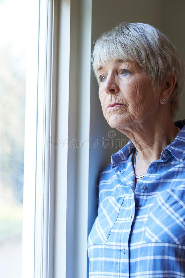 Donna senior che soffre dalla depressione che guarda dalla finestra immagini stock