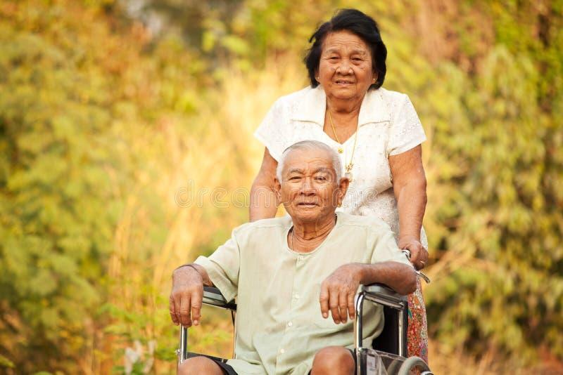 Donna senior che spinge il suo hasband disabile sulla sedia a rotelle fotografia stock