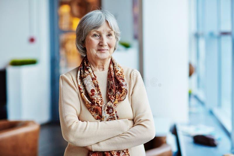 Donna senior che sta all'interno fotografie stock libere da diritti