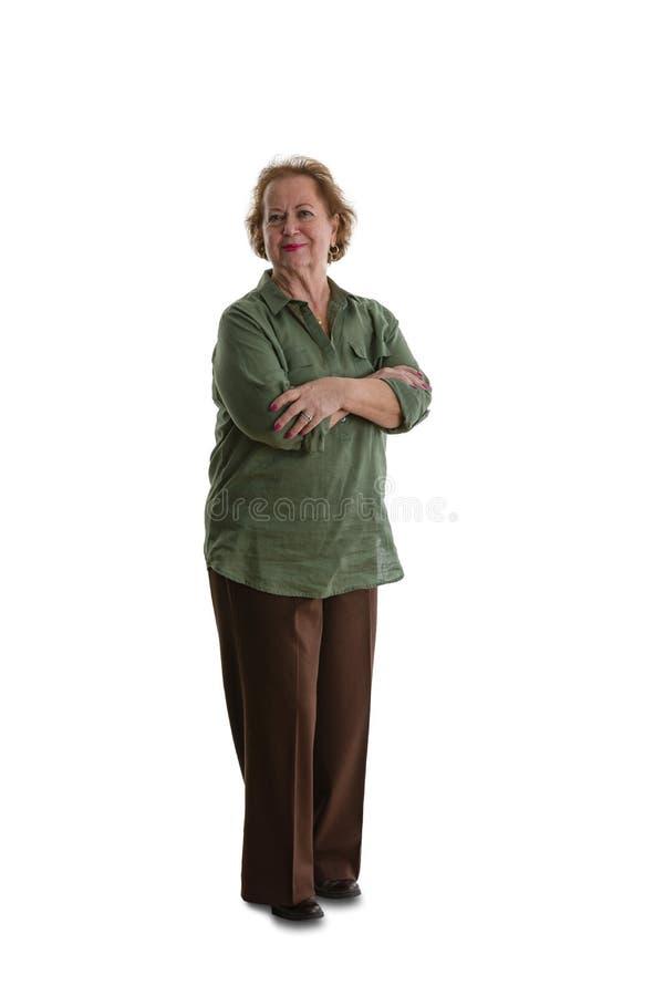 Donna senior che sta sul fondo bianco immagini stock
