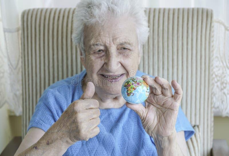 Donna senior che tiene un globo fotografia stock libera da diritti