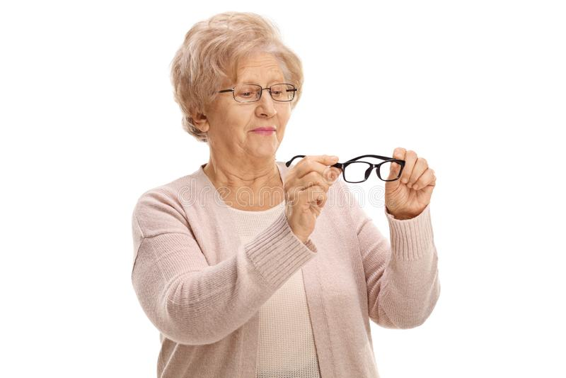 Donna senior che tiene un paio di nuovi vetri per vista e che li esamina fotografia stock libera da diritti