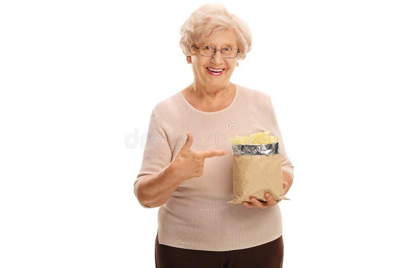 Donna senior che tiene una borsa dei chip fotografia stock