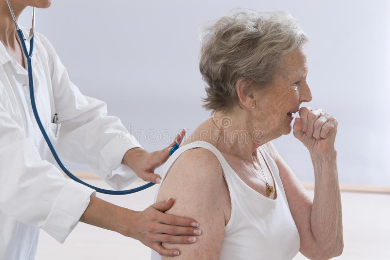 Donna senior che tossisce mentre il dottore Examining Her fotografia stock libera da diritti