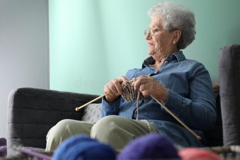 Donna senior che tricotta sciarpa calda a casa fotografia stock libera da diritti