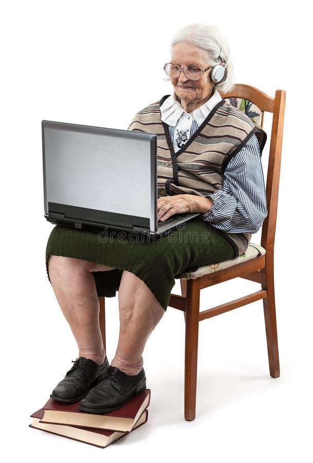 Donna senior che usando bianco del ower del computer portatile immagini stock