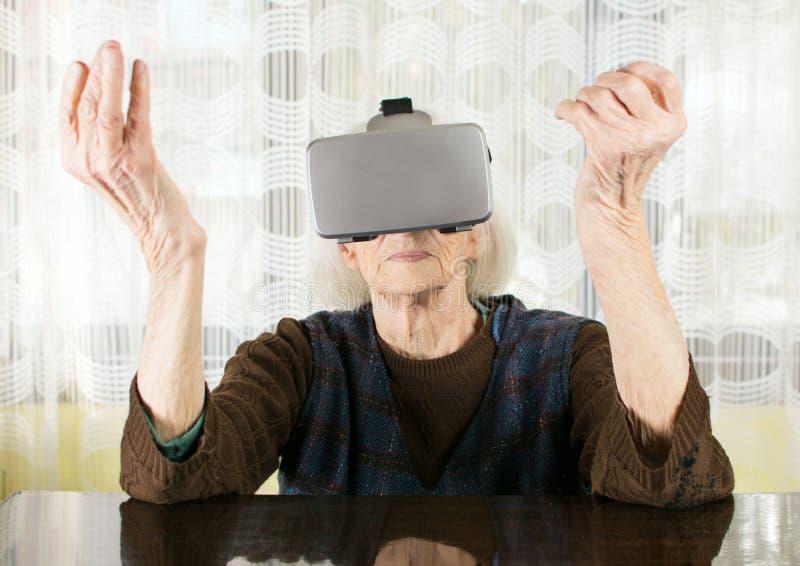 Donna senior che usando gli occhiali di protezione di realtà virtuale fotografie stock libere da diritti