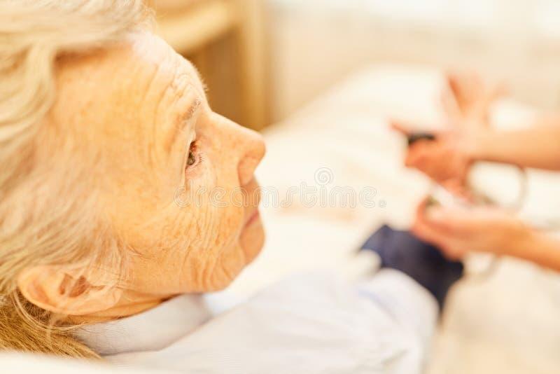Donna senior come paziente nella misura di pressione sanguigna fotografia stock libera da diritti