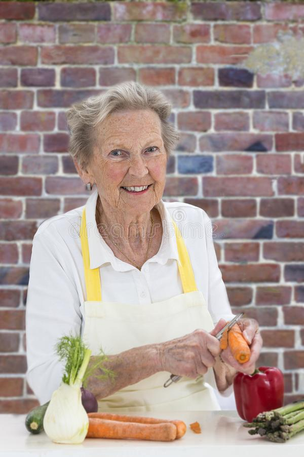 Donna senior con capelli grigi che cucina nella vecchia cucina rossa del muro di mattoni - verdure fotografia stock