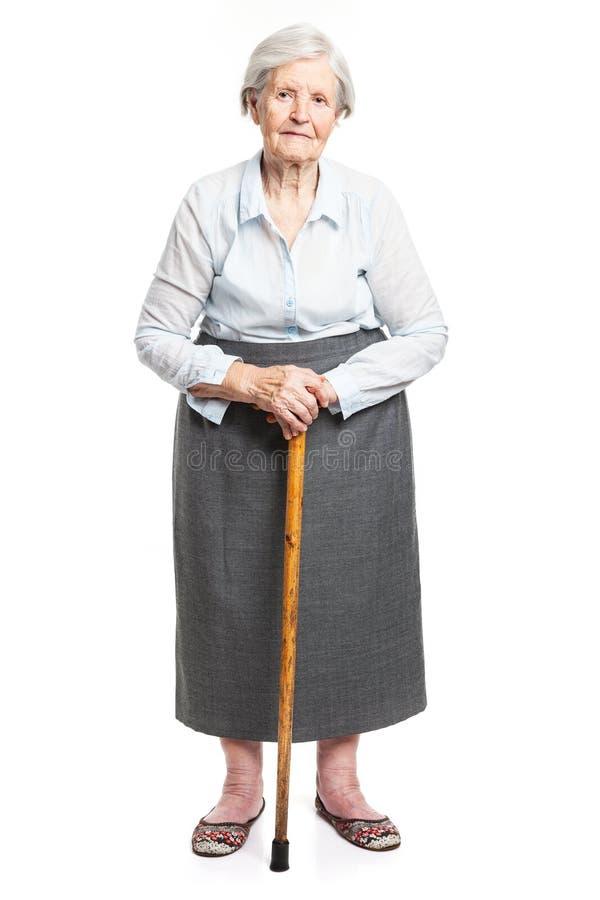 Donna senior con il bastone da passeggio che sta sul bianco fotografia stock