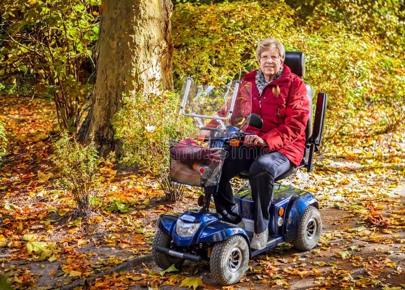 Donna senior con il motorino nel parco immagine stock