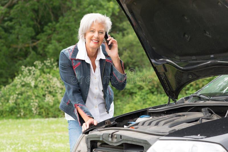 Donna senior con l'automobile rotta fotografia stock libera da diritti